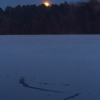 A full moonrise over a frozen lake